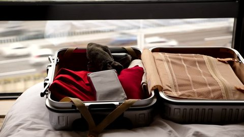 Time lapse shot of packing up small suitcase, clothes and personal items thrown into. Case lie on bed against window, car traffic seen blurred outside through glass