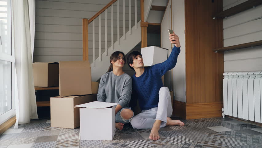 Pretty young lady and her husband are making online video call with smartphone during relocation. People are showing new house keys and boxes, talking and smiling. | Shutterstock HD Video #1025115416