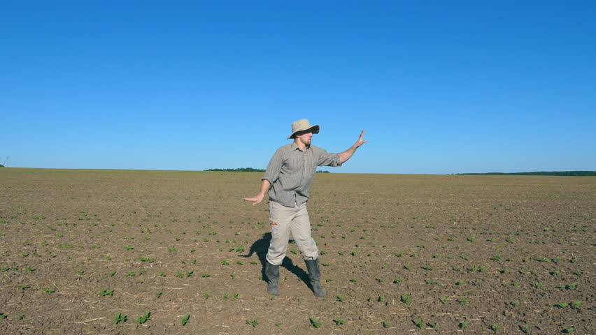 Happy male farmer dances funny among small green sprouts at the field on sunny day. Young man enjoying and having fun on meadow against the background of blue sky. Close up