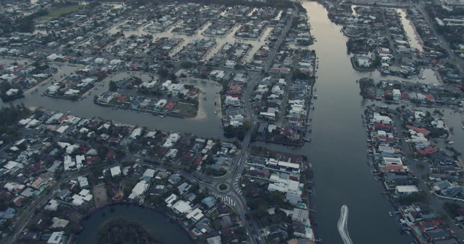 Aerial dusk view of speed boat canal waterway luxury residential homes with pontoon moorings Gold coast suburbs and property Queensland #1025142716