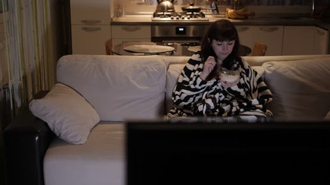 woman in the evening at home alone sitting on the couch watching tv and eating ice cream