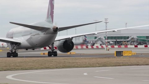 Prague, czech republic - march 3, 2019: boeing 787-8 dreamliner of qatar  airways for 254 passengers, slow motion moving on a runway and a wing with  an airplane engine draining hot rippling waves air