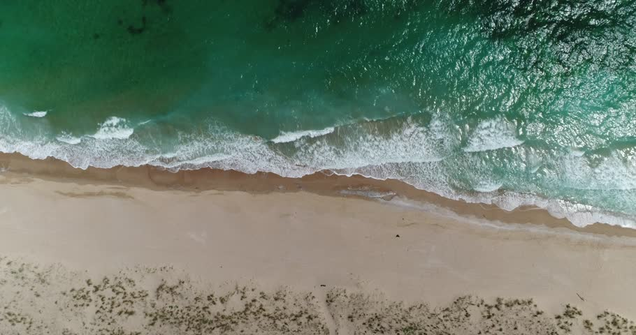 Aerial drone footage of waves reaching shore. Beach on top view.  | Shutterstock HD Video #1025205716