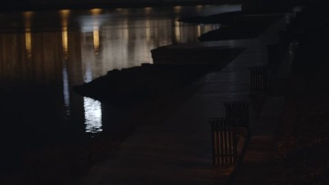 City path at quay with benches at night. Empty benches standing on embankment on background of reflected in water lights of city