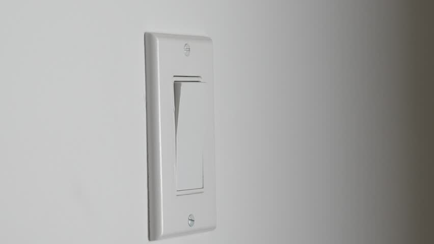 Hand Turning A Light Switch On The Wall
