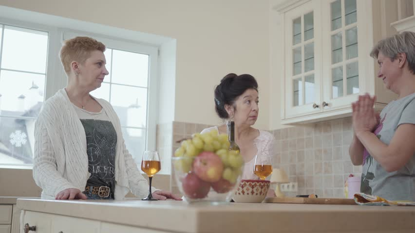 Adult cheerful girlfriends laugh and have fun chatting around the table with fruit and wine in the kitchen. Elderly girlfriends have not seen each other for a long time and are happy to talk. | Shutterstock HD Video #1025235536