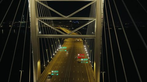 Night aerial view of highway bridge. Self or autonomous driving. Cars connected in a network. Graphic icons of fake data of the cars and drivers