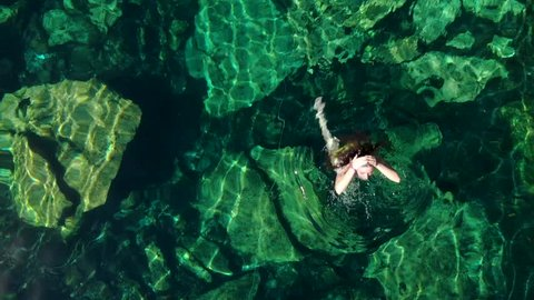 Young brunette woman floats and plays in a natural pool of a cenote in Mexico.