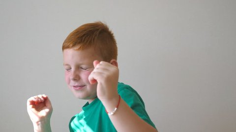 Handsome cute kid dancing with raising hands indoor. Happy male child closing his eyes and enjoy to rejoicing achievement. Portrait of red-haired boy with freckles having fun inside. Slow motion