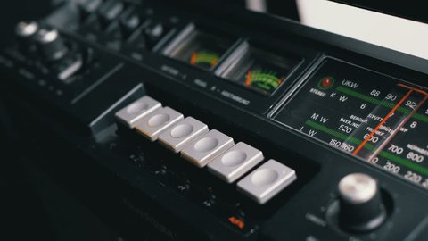 Pushing Play, Stop, Rec, ff, Rew Buttons on a Tape Recorder. Buttons on Transistor Retro Radio. Close-up. Male Finger Pushes playback control buttons on audio cassette player.