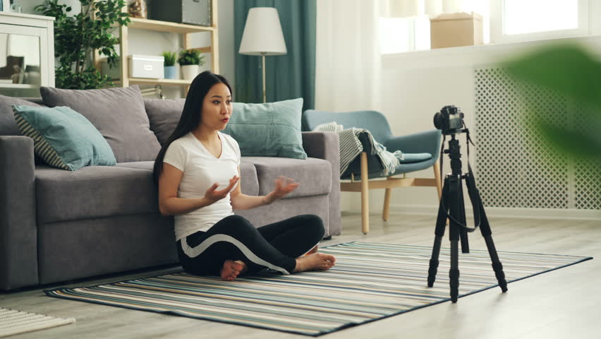 Joyful Asian woman popular blogger is recording video using professional camera talking then showing thumbs-up and waving hand to her followers. Vlogging and technology concept. | Shutterstock HD Video #1025368856