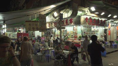 Chinese restaurant at Temple street night market, Hong Kong. Busy asian night market. Gimbal tracking shot - October 2018: Hong Kong, China