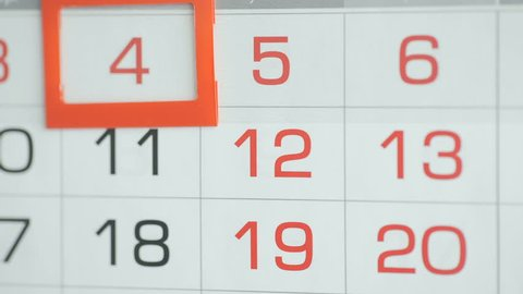 Woman's hand in office changes date at wall calendar. Changes 4 to 5