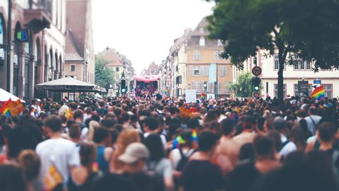 STRASBOURG, FRANCE - CIRCA 2018: Cinematic color grading over large crowd of people following gay pride truck at annual FestiGays pride gays and lesbians parade marching French streets fun atmosphere