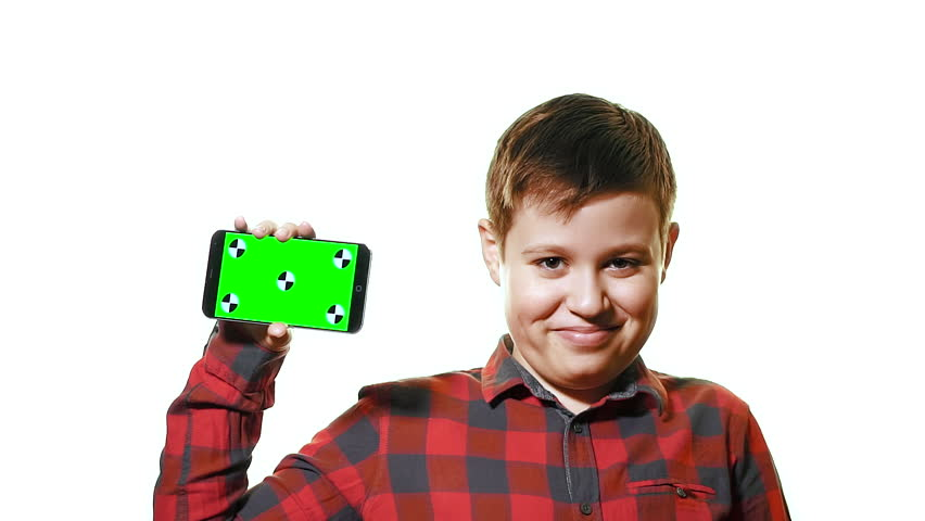 Concept mockup. Cheerful boy holding a smartphone in his hand with a green screen and laughs. It is on a white background and slow motion | Shutterstock HD Video #1025453336