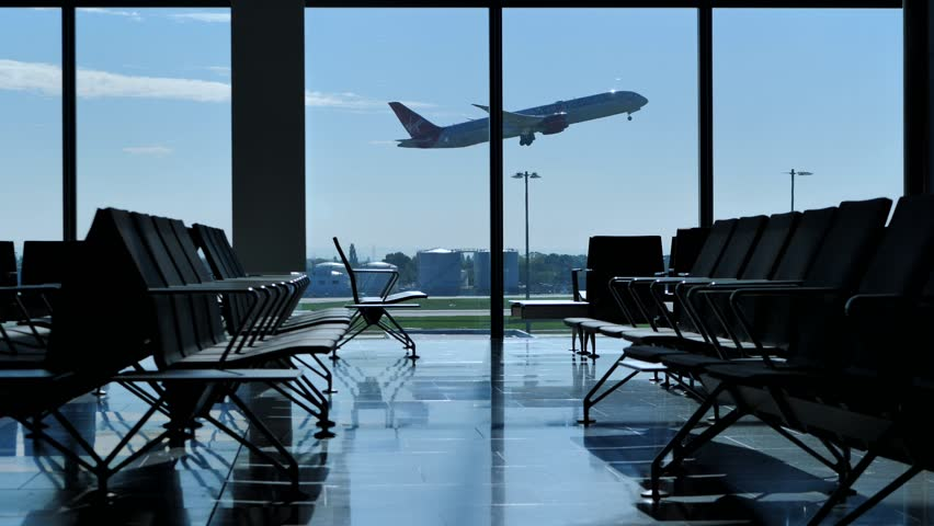 Airplane taking off seen through window. View from inside terminal waiting hall benches. | Shutterstock HD Video #1025512166