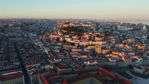 Aerial view; drone flight forward to the ancient building with brown rooftops; sunset time in Lisbon; beautiful winter evening in Portuguese capital; Alfama oldest historic district; view from above