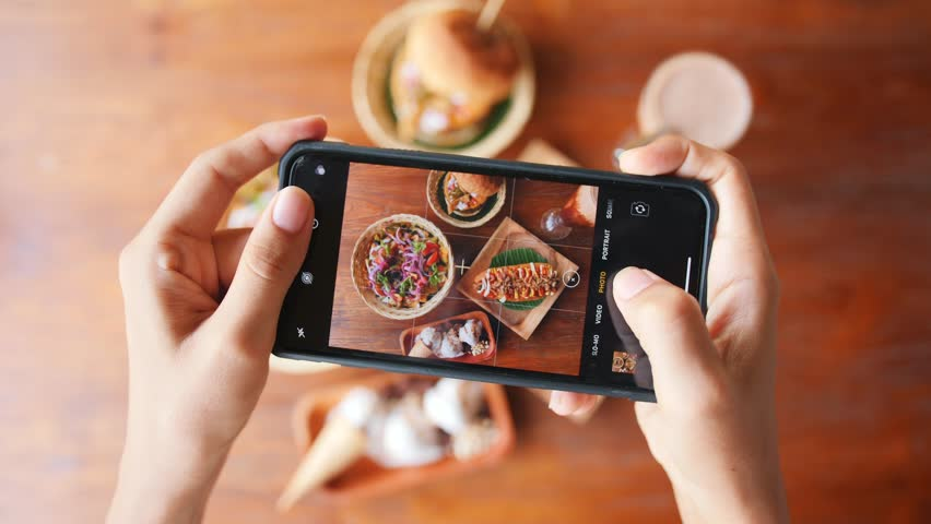 Female Taking Photo of Fast Food Using Mobile Phone in Vegan Restaurant. 4K Slowmotion Flatlay Food Photography on Wooden Table in American Diner. Bali, Indonesia. #1025545676