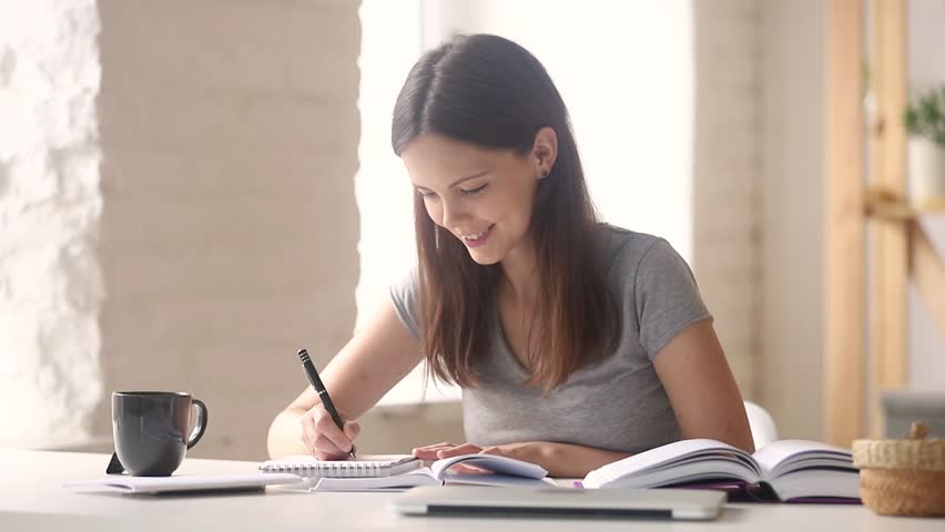 Teen girl high school college university student learning making notes writing essay in notebook doing academic research preparing for exam coursework work with books sitting at desk studying at home
