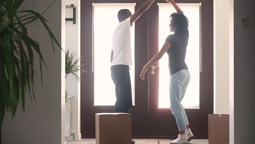 Happy african american couple first time home buyers dancing in hallway moving with boxes celebrate relocation buy new house, excited black family tenants renters having fun enjoy renovation mortgage