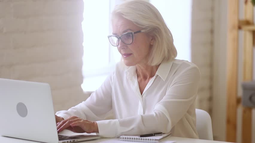 Old middle aged businesswoman working with laptop and papers, busy senior mature woman paying bills online banking managing finances checking budget doing paperwork using computer sitting at desk | Shutterstock HD Video #1025577116