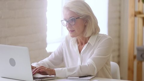 Old middle aged businesswoman working with laptop and papers, busy senior mature woman paying bills online banking managing finances checking budget doing paperwork using computer sitting at desk