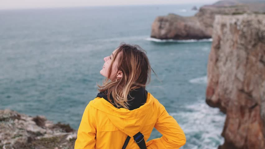 Woman Looking At The Stormy Ocean View, Standing On The Cliff Edge. SLOW MOTION. Traveler Girl relaxing, thinking, dreaming, enjoying nature. Peace and calm landscape, windy weather. | Shutterstock HD Video #1025587346