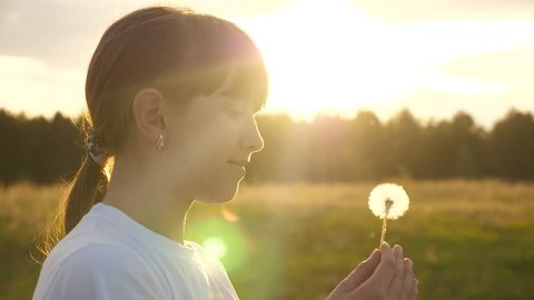 beautiful girl blowing on dandelion fluff slowly flying through air, slow motion. happy childhood concept