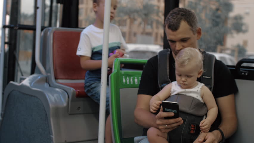 Dad riding in the bus with elder son and one year old baby daughter. Everyone watching fathers smart phone