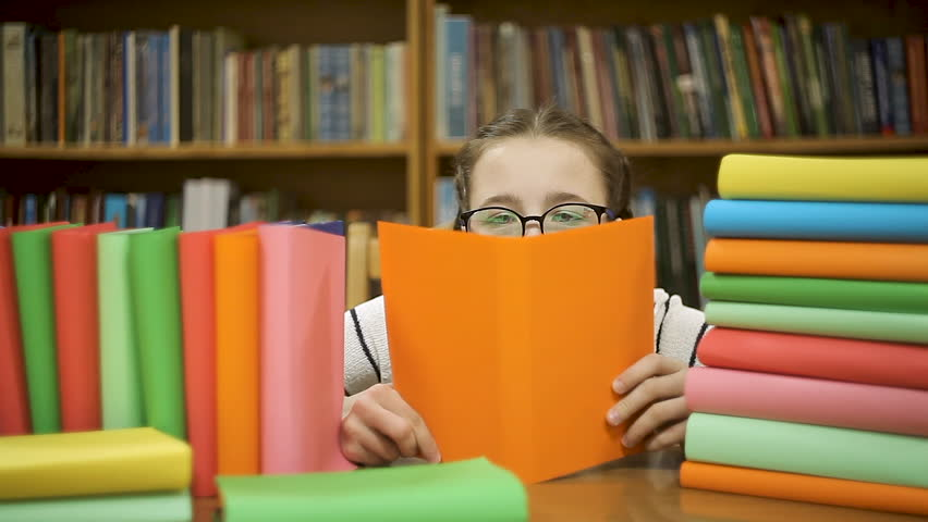 Little girl in big glasses hides behind a book, reads a book