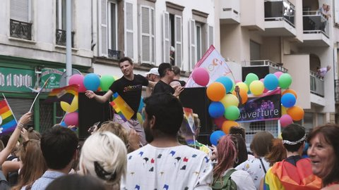 STRASBOURG, FRANCE - CIRCA 2018: Gay truck with people dancing and large crowd of people waving rainbow flags at annual FestiGays pride gays and lesbians parade marching French streets