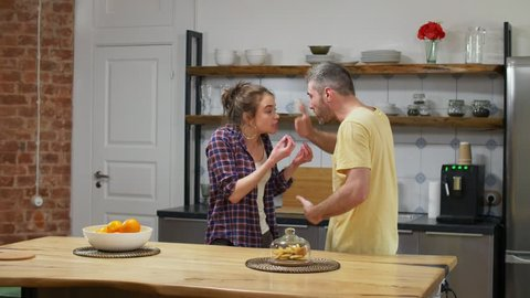 Caucasian couple very emotionally quarreling in kitchen. Relationship difficulties and problems concept