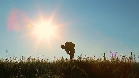 Black silhouette of adult european man travelling alone at countryside. Tired man stops, wiping his sweat from forehead and continuous walking. Sunset sunny blue sky background Real time video footage