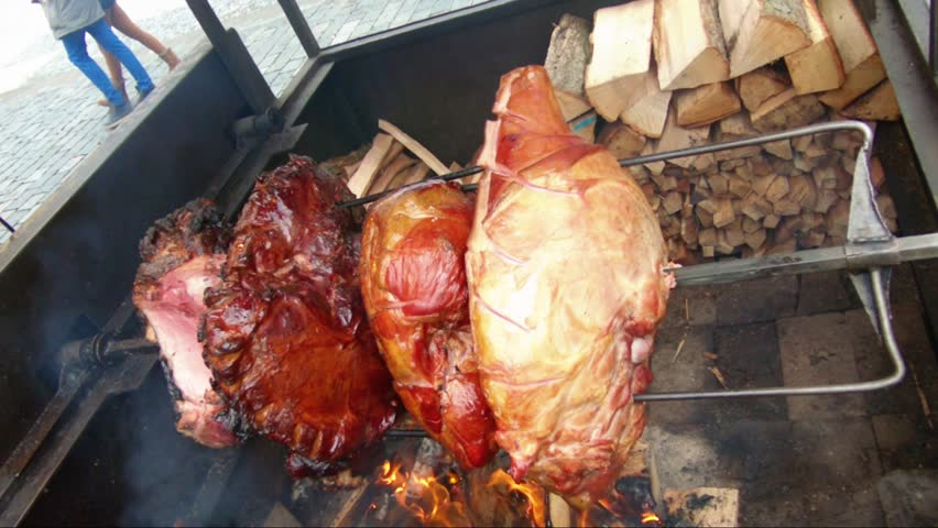Big pieces of prague ham spit roasting on a street market | Shutterstock HD Video #1025672906