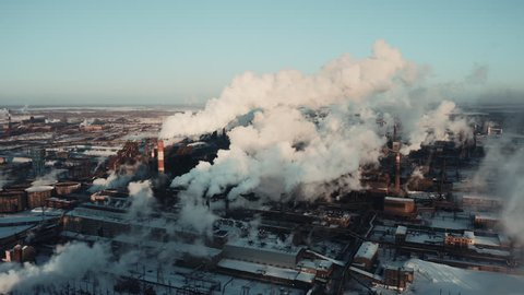 Drone extremely near flight between several steel plant tubes through the clouds of smoke, industrial park landscape in winter snowy evening, air emissions from manufacturing sector, Chelyabinsk
