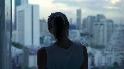 Beautiful woman admire cityscape view standing by window at home