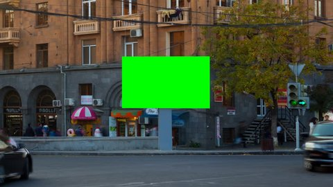 4K TIME LAPSE VIDEO. Advertising Billboard with green screen with long exposure cars in city, against backgrounds buildings with balconies, windows and signs shops