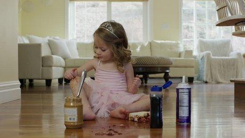 Medium shot of ballerina girl spreading food on knee and floor / Cedar Hills, Utah, United States