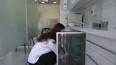 Close-up scene of a young pretty female dentist who is getting a dental instruments in a metal boxes out of a closet. Woman is absolutely confident and calm about her work.