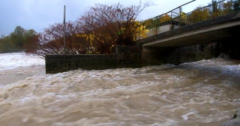 Fast flowing dirty brown flood water gushing into the river through a canal.