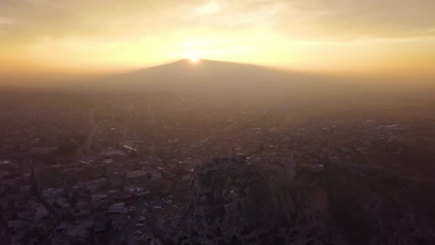 Drone footage flying top down slowyly, zooming in Uchisar Forstress, Turkish flag waving on top, Cappadocian houses in the background, during golden hour, in Nevsehir, Turkey   Shutterstock HD Video #1025734826