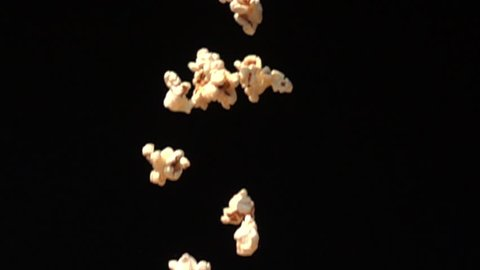 Popcorn falling down to the ground on black background in Slow Motion