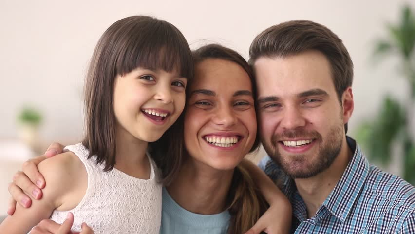 Happy family of three mom dad and cute child little daughter embracing laughing looking at camera, smiling young parents with kid girl having fun hug enjoy sincere communication warm relationships