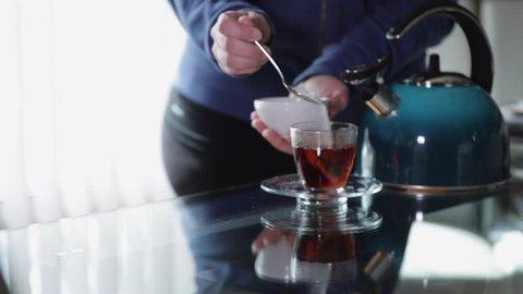 Woman adding sugar to tea