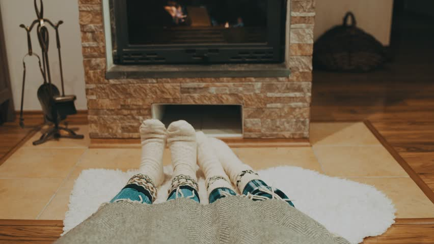 Couple resting by fireplace, Cheerful mother and child at home in knitted socks, near the fire, winter, christmas time | Shutterstock HD Video #1025842076