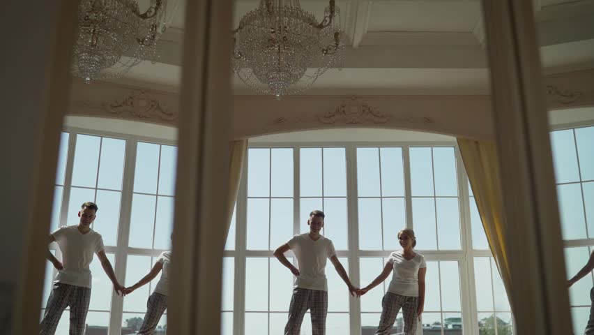 Romantic couple at home. Attractive young woman and handsome man are enjoying spending time together. Young couple dancing on the windowsill. | Shutterstock HD Video #1025861786