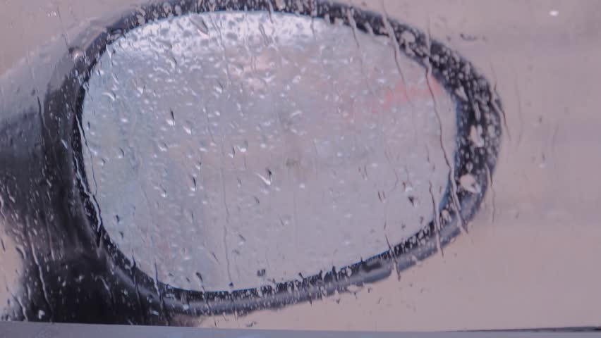 View of car mirror from inside the car, rain on the window   Shutterstock HD Video #1025866706