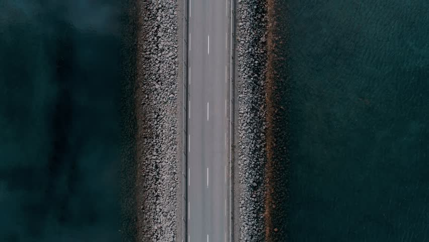 Slow motion aerial straight down drone shot of highway brdge leading through crystal clear water or marina bay. rare ocassional commuter or tourist traffic, electric car pass by | Shutterstock HD Video #1025887946