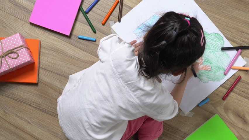 The Asian little girl is drawing the picture in the paper on the wooden ground she has many book and color pencil around her, top view of child on floor, Educational concept for school kids | Shutterstock HD Video #1025893166