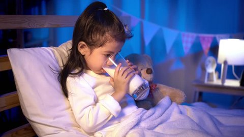 Child asian girl drinking some milk on bed in a dark bedroom at night before sleeping, Comfortable children at home concept